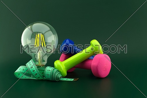 Starting healthy lifestyle concept with lamp light bulb, dumbbell weight and measuring tape over a dark green background