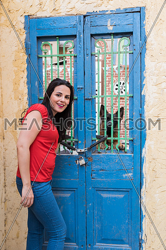 young lady standing beside old locked door, and dog behind the door