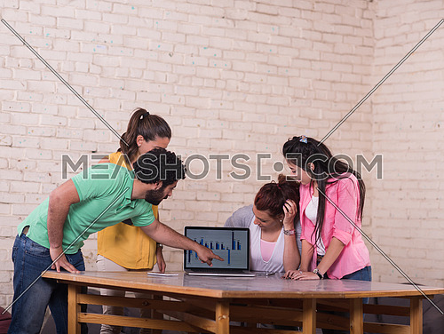 informal group of young middle eastern businessmen having a meeting while using a laptop in a modern office