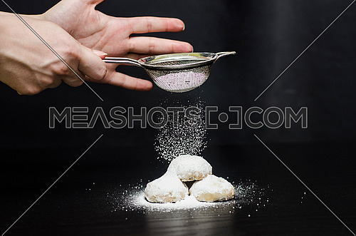 a lady sprinkling sugar from a sprinkler on top of 3 kahk pieces on a black table