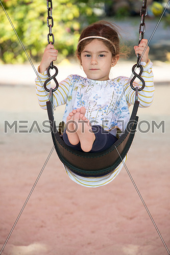a little girl swinging alone in an outdoor park