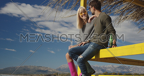 Couple Drinking Beer Together on beach during autumn time