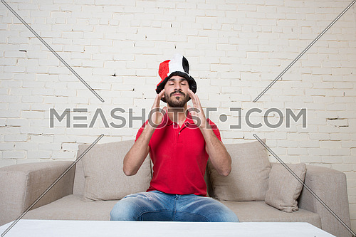 young man watching football game wearing Egyptian flag hat