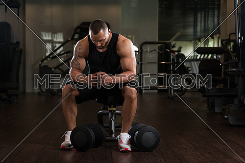 Healthy Bodybuilder Resting In Healthy Club After Exercising