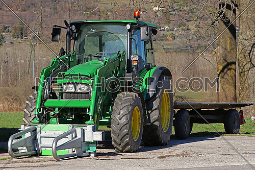Green tractor and flatbed trailer