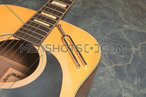 Acoustic guitar on a green marble background, on the guitar there is a tuning fork, music concept.