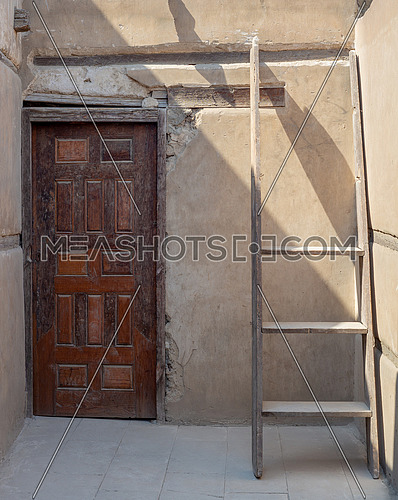 Stone wall with wooden grunge old decorated door and broken wooden ladder, Cairo, Egypt