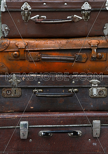 Stack of four old vintage antique grunge travel luggage brown leather suitcase trunks, close up, low angle front view