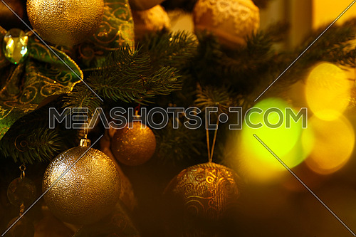 Close up handmade decorations hanging Christmas tree, bows, balls, spheres in warm light, front view