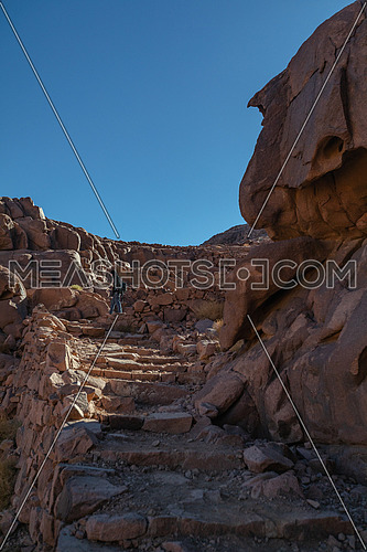Long shot for stairs made of rock and a tourist standing on