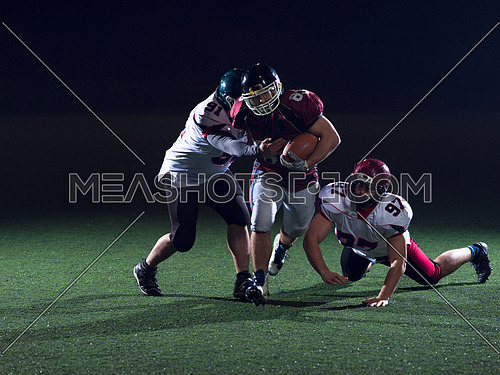 American football players in action at night game time on the field