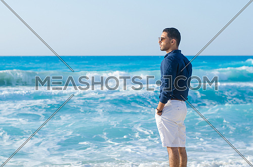 a young man wearing shorts and shirt standing looking towards the sea