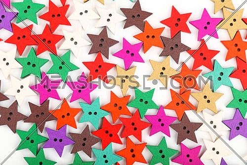 Close up background pattern of colorful multicolor handmade wooden sewing buttons on white background, elevated top view, directly above