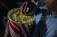 Close up for black young man eating popcorn at movie theatre.