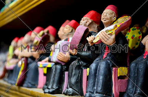 small statues of old men playing on music instruments, oriental music