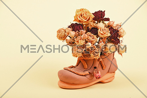 Dried red and yellow roses flower bouquet in small ceramic shoe on tender yellow paper background
