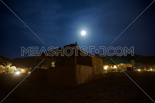 low angle for a Wicker tent in a campe in Sinai at the night with full moon.
