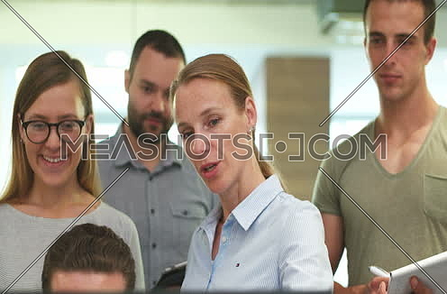 Blond woman doing presentation to Business Partners In Modern Office at day