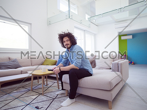 young handsome man enjoying free time watching television in his luxury home villa