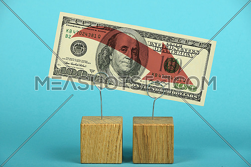 US crisis, decline of American dollar, one hundred US dollars banknote with red arrow down on wooden metal holders over blue