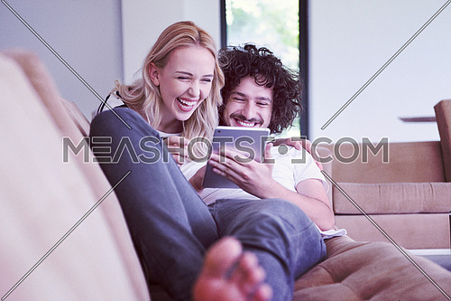 Young couple relaxing at luxurious home with tablet computers reading in the living room on the sofa couch.