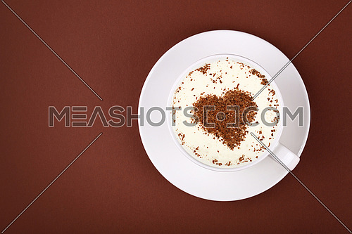 Close up white cup full of latte cappuccino coffee with heart shaped chocolate on milk froth at porcelain saucer over brown paper background, close up, elevated top view, directly above
