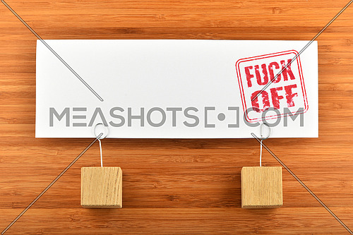 Fuck off red rude stamp on one big white paper note with two wooden holders on wooden bamboo background for presentation