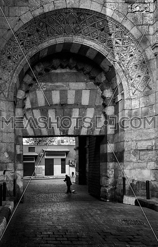 a man sweeping the street under the gate arch of El Moez ST cairo Egypt