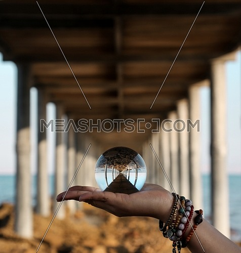 Close up for female hand holding a crystal ball underneath a bridge at day