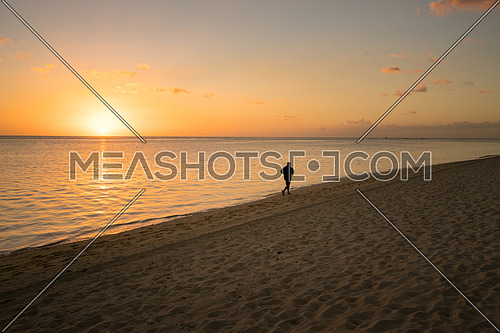 One silhouette running alone on the beach at sunset in Mauritius.