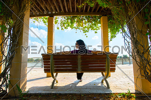 A girl sitting on a bench shot from the back