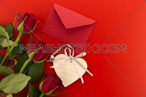 Red roses, envelope and wooden heart medallion on red background with free copy space. Wishes, greetings and love message
