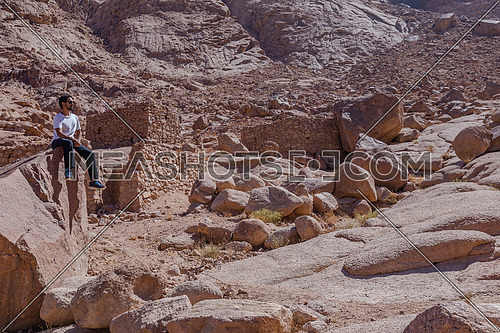 Long shot for man stting down on rocks in Sinai Mountain - Frej Vally by day