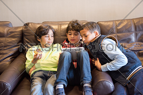 Young middle eastern boys are having fun with the tablet in the living room