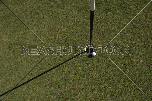 top view of golf ball on edge of course hole representing achivement and success business concept