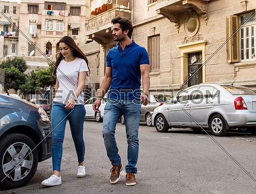 A young man and a lady walk in the street in the morning