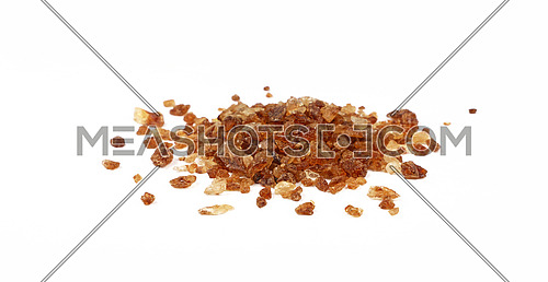 Pinch of big brown caramel candy sugar crystals spilled around isolated on white background, close up, low angle view
