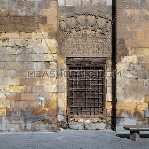Daylight shot of grunge wooden window with decorated iron grid over stone bricks wall and marble garden bench, Moez Street, Cairo, Egypt