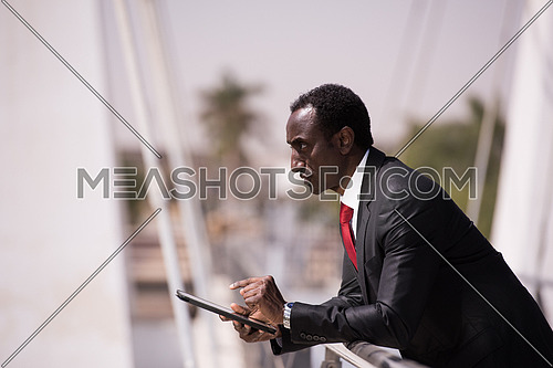 portrait of young african american businessman on bridge while working on tablet computer