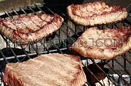 Grilled beef bbq steaks cooking roasting on outdoors flame barbecue grill, poured and dredged with salt