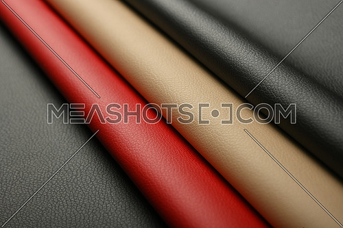 Close up background of black, red and beige white natural leather grain, high angle diagonal view