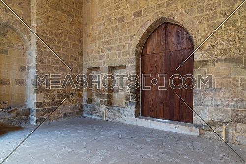 Arched wooden door and two embedded niches in stone bricks wall, at the public Mosque attached to Al-Muayyedi Bimaristan historic building, Darb Al Labana district, Old Cairo, Egypt