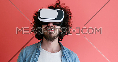 Happy man getting experience using VR headset glasses of virtual reality, isolated on red background