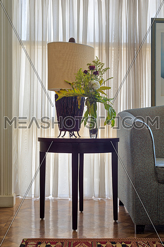 Interior shot of  table lamp and colorful flowers planter on small dark brown wooden table on background of big window with white sheer curtains and grey armchair