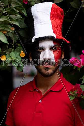 An Egyptian male painted Egyptian flag on his face with a hat on his head