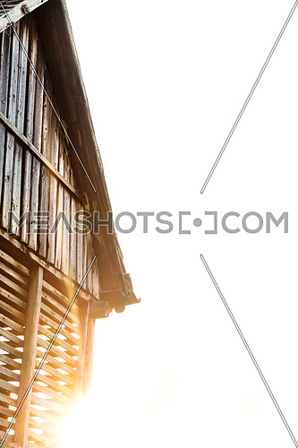 Old wooden barn and the sun