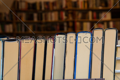 Hardcover books back edges on wooden shelves display of retail book store or shop over close up