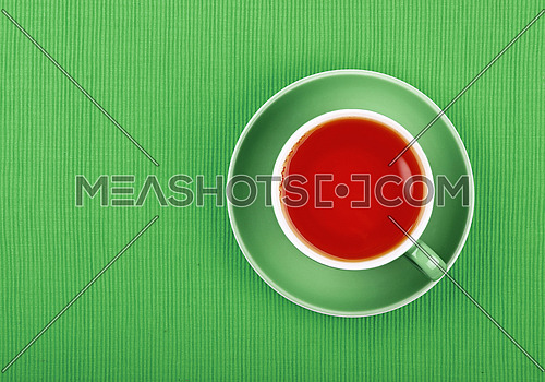 Full cup of black tea on saucer over natural green textile tablecloth, close up, elevated top view
