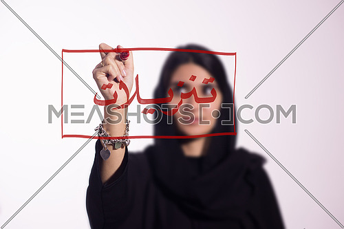 Arabian middle eastern business woman writing with a marker on virtual screen in arabic SALE or Discounts isolated on white background