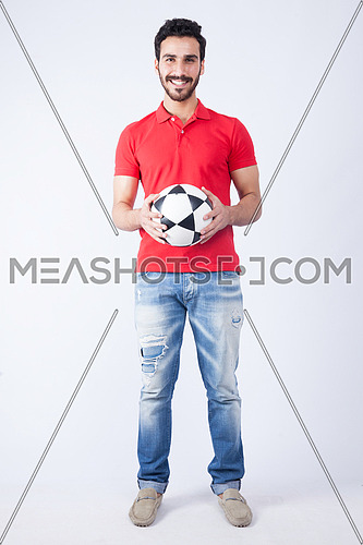 A young man wearing red t-shit and holding a football on a white background